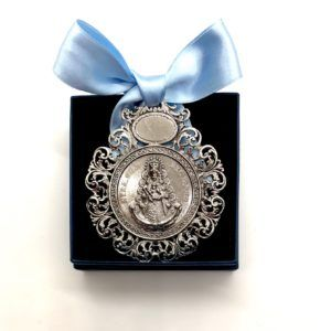 Medalla cuna de la Virgen del Rocío fundida con motivos inspirados en filigrana. Aparece la virgen con sus galas de reina