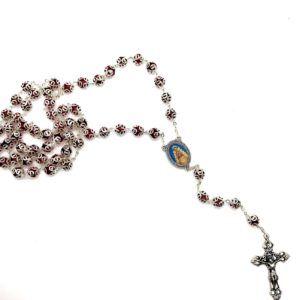 Rosario Virgen del Rocío formado por cuentas grandes y redondas fabricadas en metal y vidrio de color burdeos. Cruz de metal.