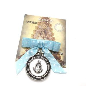 Medalla de cuna de la Virgen del Rocío realizada en Zamak. Incluye lazo de lunares de color azul con soporte en la parte posterior.