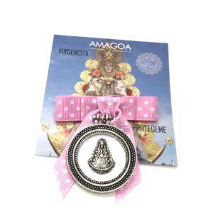 Medalla de cuna de la Virgen del Rocío realizada en Zamak. Incluye lazo de lunares de color rosa con soporte en la parte posterior.