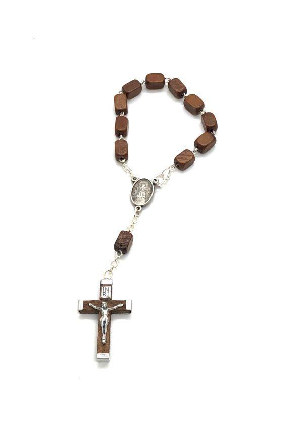 Rosario de mano de la Virgen del Rocío formado por 11 cuentas rectangulares de madera en color marrón. Cruz de madera y metal.