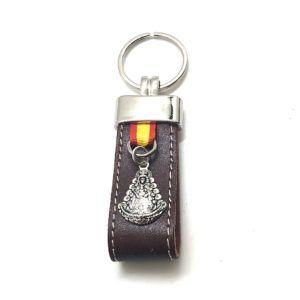 Llavero fabricado en cuero de color marrón con colgante de la Virgen del Rocío y cinta de la bandera de España. Material de fabricación: Acero inoxidable y cuero.