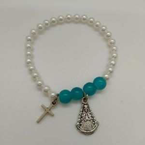 Pulsera Niña Virgen del Rocío perlas, blancas y turquesa. Medalla colgante Cruz y silueta Virgen del Rocío. Elástica y metal.