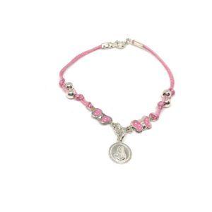 Pulsera cordón de color rosa. Incluye medalla redonda de la Virgen del Rocío y dos mariposas a cada lado esmaltadas en rosa con puntos blancos.